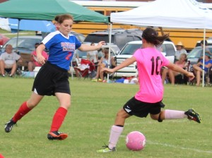 CCMS midfielder Allie Amado(right) centers the ball against the defense of a DeKalb County defender in Saturday's scrimmage