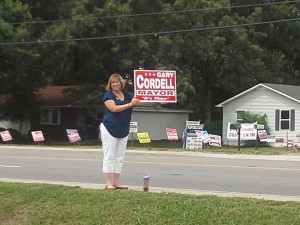 A supporter of Mayoral candidate Gary Cordell shows her sign to travelers on Hwy 55 on Saturday