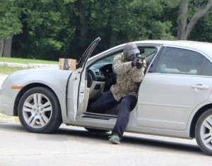 """Manchester assistant Police Chief Adam Floied exits the vehicle with weapon drawn as a """"bad guy"""" during a STOPS tactical scenario.. Photo by Dennis Weaver"""