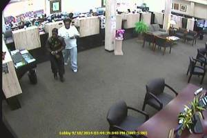 The two suspects leaving  the bank counter