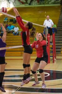 Sydney Pearson goes up for a block as Valaina Barger(#18) protects against the cross in a recent match... Photo by John St Clair