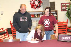 Brianna Jones signs with the Southern Illinois Salukis. Her parents watching proudly as she signs... Photo by Barry West