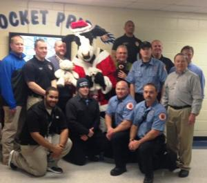 Members of the Manchester Police Department and Manchester Fire Department pose with the Chik-Fil-A cow on Thursday night for the for the Teddy Bear Toss - Photo Provided