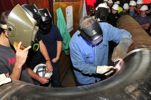 Grundy County High School welding class students watch as AEDC craftsman Chester Stovall works with a tungsten inert gas (TIG) welder. (Photo by Rick Goodfriend)
