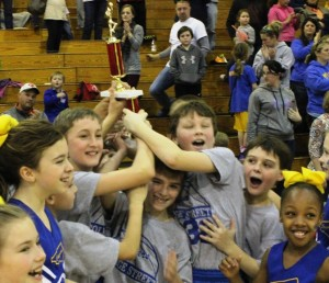 The College Street Cougars boys basketball team celebrates their 2015 CCYBL championship on Saturday