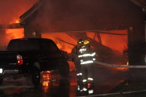 Firemen fighting the blaze with a pickup near by.