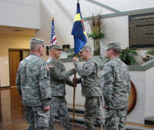 Outgoing first sergeant, 1st. Sgt. Greg Sawyer (second from left), hands the Headquarters and Headquarters Detachment, 30th Troop Command, Tennessee Army National Guard, guidon to Command Sgt. Maj. Greg Turner during a formal change of responsibility for the unit, held Feb. 8, 2015. Sawyer relinquished his position as the unit's first sergeant to incoming 1st Sgt. Kenneth Latham (right) while Sgt. 1st Class Ronald Cannon (left) the unit's guidon bearer, oversees the traditional exchange. (U.S. Army National Guard photo by Sgt. Sarah Holt, released.)