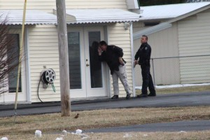 Coffee County Sheriff Investigator looks in the door at Henley and Son TV with Manchester Police Officer Dustan Foster providing backup... Photo by Barry West