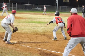 Garrett Davis of Coffee County Middle(#27) gets a lead at first base on Thursday night against North Franklin.  Coach Rodney Meeker gives instruction in the foreground(right)