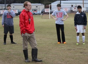 Andy Escue, CHS assistant soccer coach, talks to his team after a recent practice on the soggy Raider Soccer Field.