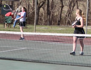 CHS tennis player Maddie Taylor(left) returns a serve against Columbia on Monday as her doubles partner, Carlee Reed(right) looks on.