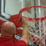 """CCMS head coach George Pearson helps """"cut down the nets"""" on Monday night to celebrate their CTC Tournament win on Saturday"""