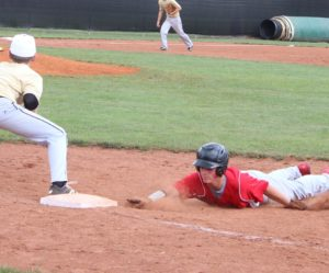 Zach Morgan dives back into 1st base to avoid a pick-off attempt against Central Magnet on Saturday.