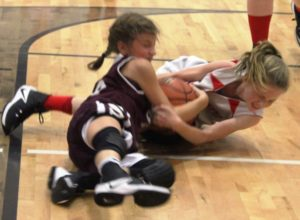 Katie Cotten of CCMS(in white) battles for a loose ball on Thursday night against White County.