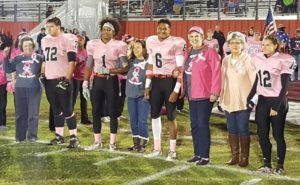 Breast cancer survivors join the CHS captains to the center of the field for the coin toss prior to Friday's game. [Photo by Brock Freeze]
