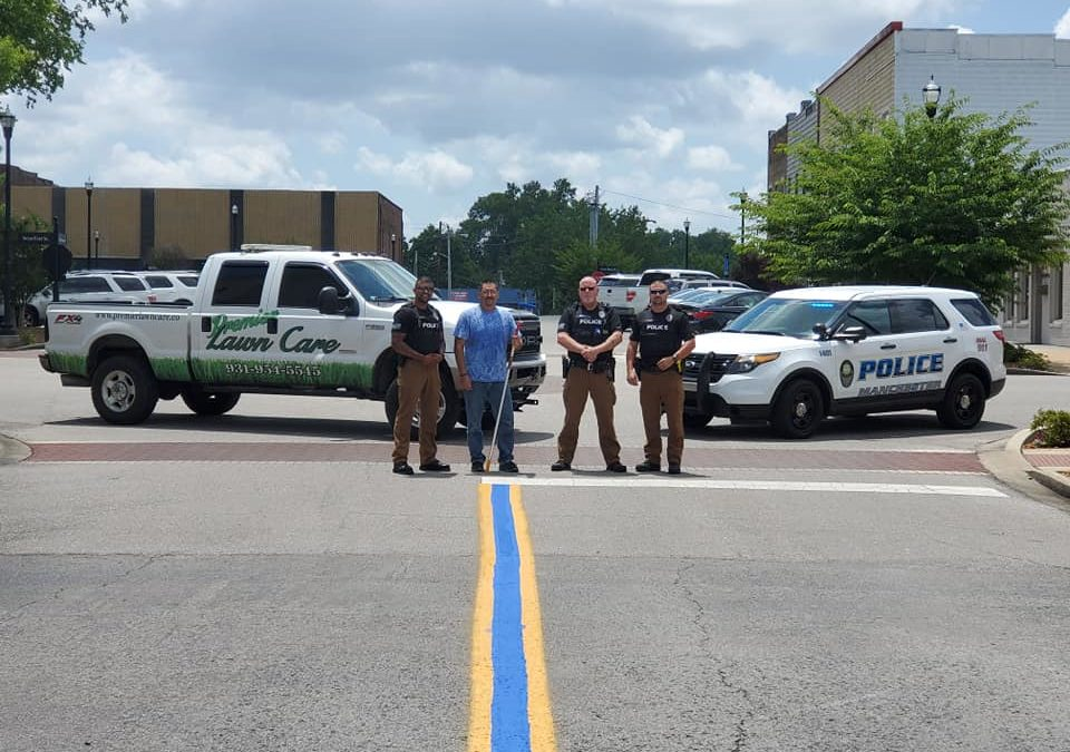 Premier Lawn Care paints blue line on N. Irwin St. in support of MPD